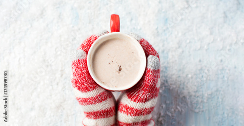 female hands in gloves holding hot chocolate