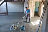 Laborer performing and polishing sand and cement screed floor. Sand and cement floor screed. - 174998944