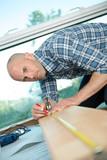 man measuring a flooring plank - 175001743