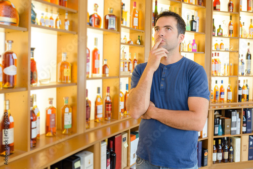 Man contemplating in liquor store Poster