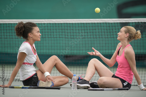 Women sat by tennis court net throwing ball into the air