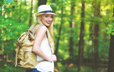 Young woman walking on a forest trail on a beautiful summer day