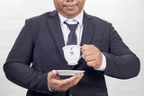 Fat businessman in a suit  who is drinking a cup of coffee. - 175018184