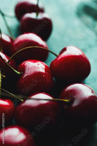 Fotobehang Kersen Close-up of shiny cherries lying on shabby green surface.