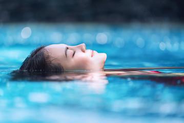 Young asian woman relaxing in swimming pool at spa resort. © Natnan