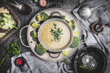 Broccoli soup in cooking pot on  rustic kitchen table background with ingredients and tools, top view - 175030517