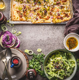Tarte flambee or open vegetable pie with vegetables and green salad on rustic kitchen table background with plates, cutlery and tools, top view, frame. Traditional German food - 175030952
