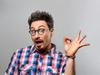 Handsome young man Having Fun Crazy. Surprised Gesturing, Open Mouth. Portrait Hipster Nerd guy in Trendy shirt, Glasses. Brunette Bearded Emotional Stylish Hairstyle on gray background. Blue Eyes