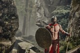 Young muscular man holding shield and spear posing in armor of ancient gladiator looking at camera on background of woods. Spartan. - 175040374