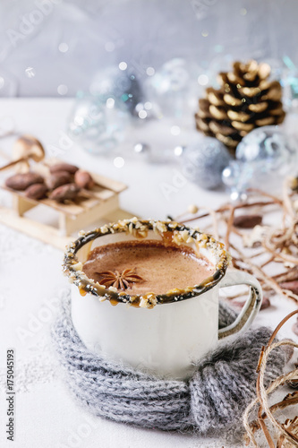 Foto op Canvas Chocolade Vintage mug in wool scarf of hot chocolate, decor with nuts, caramel, spices. Ingredients and Christmas toys above over white texture background with space.