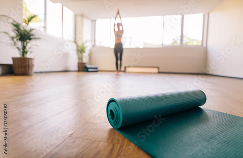 Sticker Exercise mat on floor with woman doing yoga