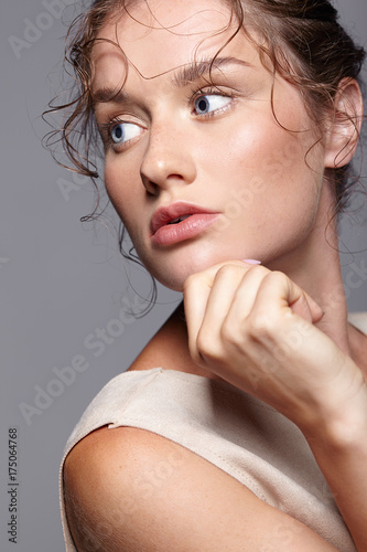 Beauty portrait of young woman. Brunette girl with bright blue eyes and day female makeup on gray background © Serg Zastavkin