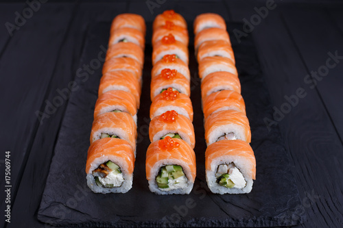 Foto op Canvas Sushi bar Delicious california sushi rolls set on black slate, restaurant serving. Japanese food art