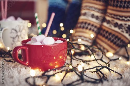 Papiers peints Chocolat Christmas lights and mug of chocolate with marshmallow on rug