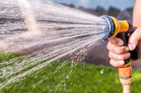 watering the grass with hose - 175076147