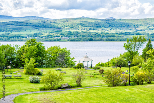 Papiers peints Vert chaux Landscape aerial view of Sainte-Famille park in summer in Ile D'Orleans, Quebec Canada by Saint Lawrence river, village houses, gazebo, picnic tables and path, trail, sky