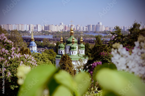 Foto op Canvas Kiev Vydubychi monastery church among blooming lilac bushes in spring. Kiev, Ukraine. Vintage film filtered photo
