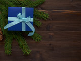 Christmas dark blue gift box tied with turquoise ribbon on spruce branches - 175079906