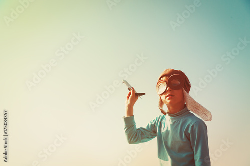 little boy with helmet and glasses play with toy plane on sky
