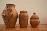 clay homemade brown vase and the pots with a beautiful carved flower on the wooden floor - 175095397