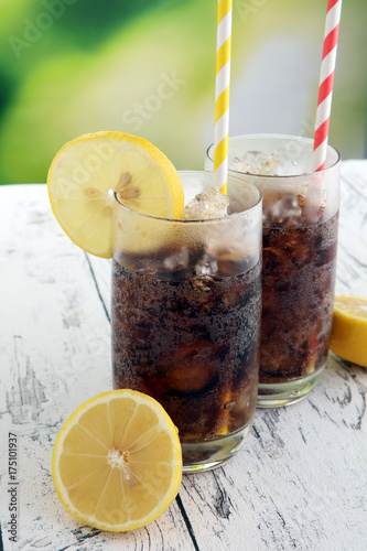 Softdrink with ice cubes, lemon and straw in glass Poster