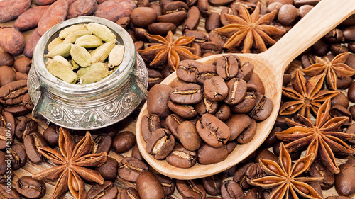 Fotobehang Koffiebonen Coffee beans in a wooden spoon with cardamom, cocoa beans and anise illicium as warm aromatic background