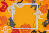 Halloween flat lay frame on orange background with copy space