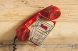 Red old fashioned telephone receiver on wooden table - 175118558