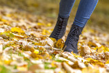 female legs in boots on autumn leaves - 175120329