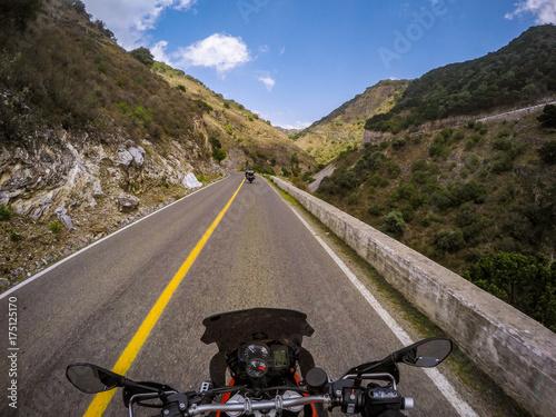 POV ridding a motorcycle on a road плакат