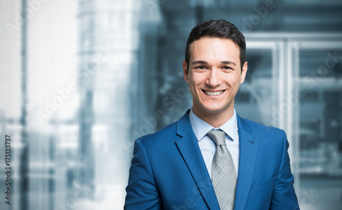 Smiling businessman in front of a blue background