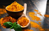 Composition with bowl of turmeric powder on wooden table - 175138910