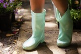 Low section of girl wearing green rubber boot standing on - 175151330