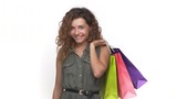 trendy curly woman admiring herself satisfied after shopping holding packs waving on camera isolated on white background. Concept of emotions - 175153513