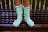 Low section of girl wearing green rubber boot standing on wooden - 175155933