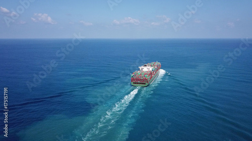 Huge large mega container ship sails on open water fully loaded with containers and cargo - aerial view