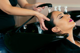 Beautiful young woman with hairdresser washing head at hair salon - 175166533