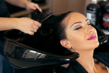 Beautiful young woman with hairdresser washing head at hair salon - 175166592