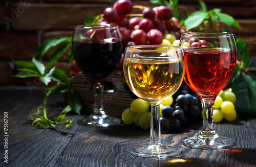 glasses of wine on dark wooden background