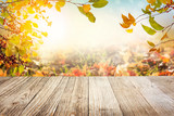 Wooden table with autumn leaves background - 175167986