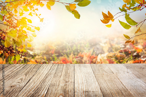 Wooden table with autumn leaves background
