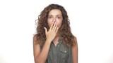 in slow motion woman in grey shirt with curly hair looking surprised frightened closing mouth with hand closeup isolated over white background. Concept of emotions - 175169597