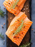 Raw salmon pieces on wooden board with herbs, salt and spices - 175176506