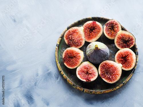 Dish of purple italian figs on gray background. Summer autumn fruit snack