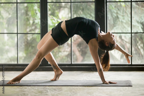 Poster Young attractive woman practicing yoga at home, stretching in Camatkarasana exercise, Wild Thing, Flip-the-Dog pose, working out, wearing sportswear, black shorts, top, full length, studio background