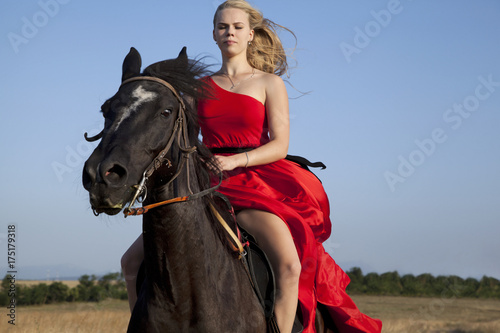 Young woman galloping on horse. Blonde in fluttering dress Poster