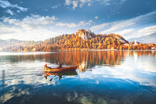 Romantic couple sailing by boat on Bled lake water in Slovenia at medieval fortress circled by colorful autumn forest background. Stunning fall scenery. Bled is famous and popular travel destination.