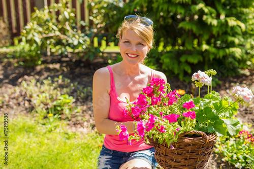 Poster Happy woman in flower garden