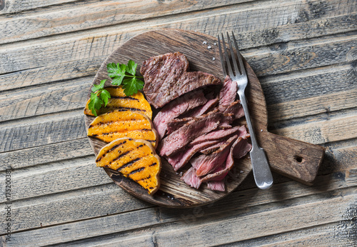 Poster Steakhouse Beef steak and grilled pumpkin on a cutting board on wooden background, top view