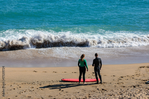 Keuken foto achterwand Barcelona Couple of surfers at the beach Barcelona, Spain